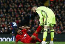 Manchester Utd:s målvakt hjälper Liverpoolspelare på traven.